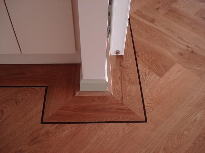 Beukers vloeren - Detail foto eiken houten vloer in visgraat motief met kader en bies
