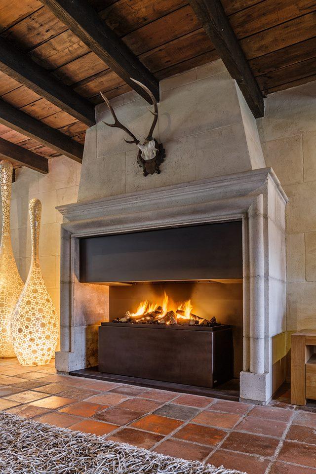Moderne gashaard ingebouwd in klassieke bestaande schouw in landelijk interieur - via Boley