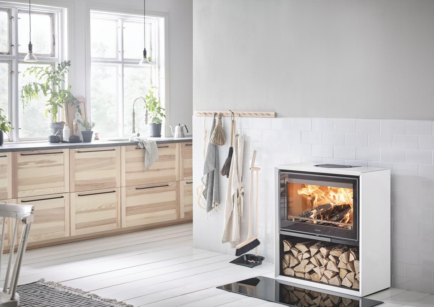 Witte houtkachel met houtopslag in houten keuken. Contura 310 kachel #houtkachel #houthaard #keuken #contura