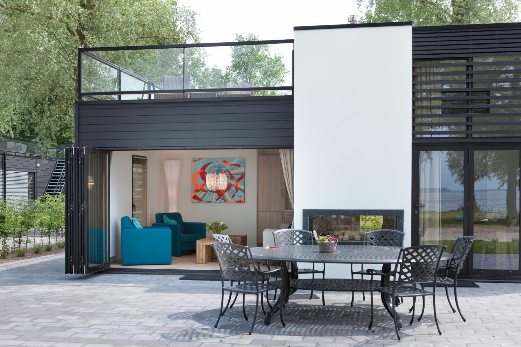 Doorkijkhaard KOTO van Wanders toegepast in de wand van een woning.  Hierdoor wordt het mogelijk om zowel buiten als binnen van de gashaard te genieten