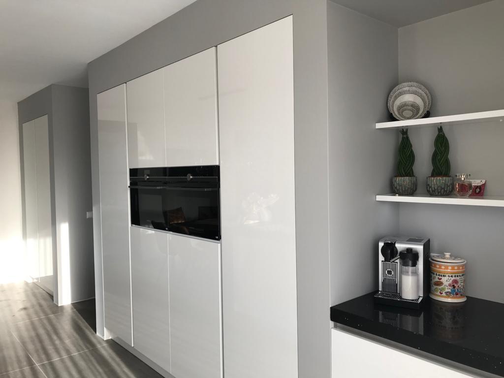 Witte keuken met hoge kast voor inbouwapparatuur. Keukens 2020. Kuhlmann keukens Vida hoogglans