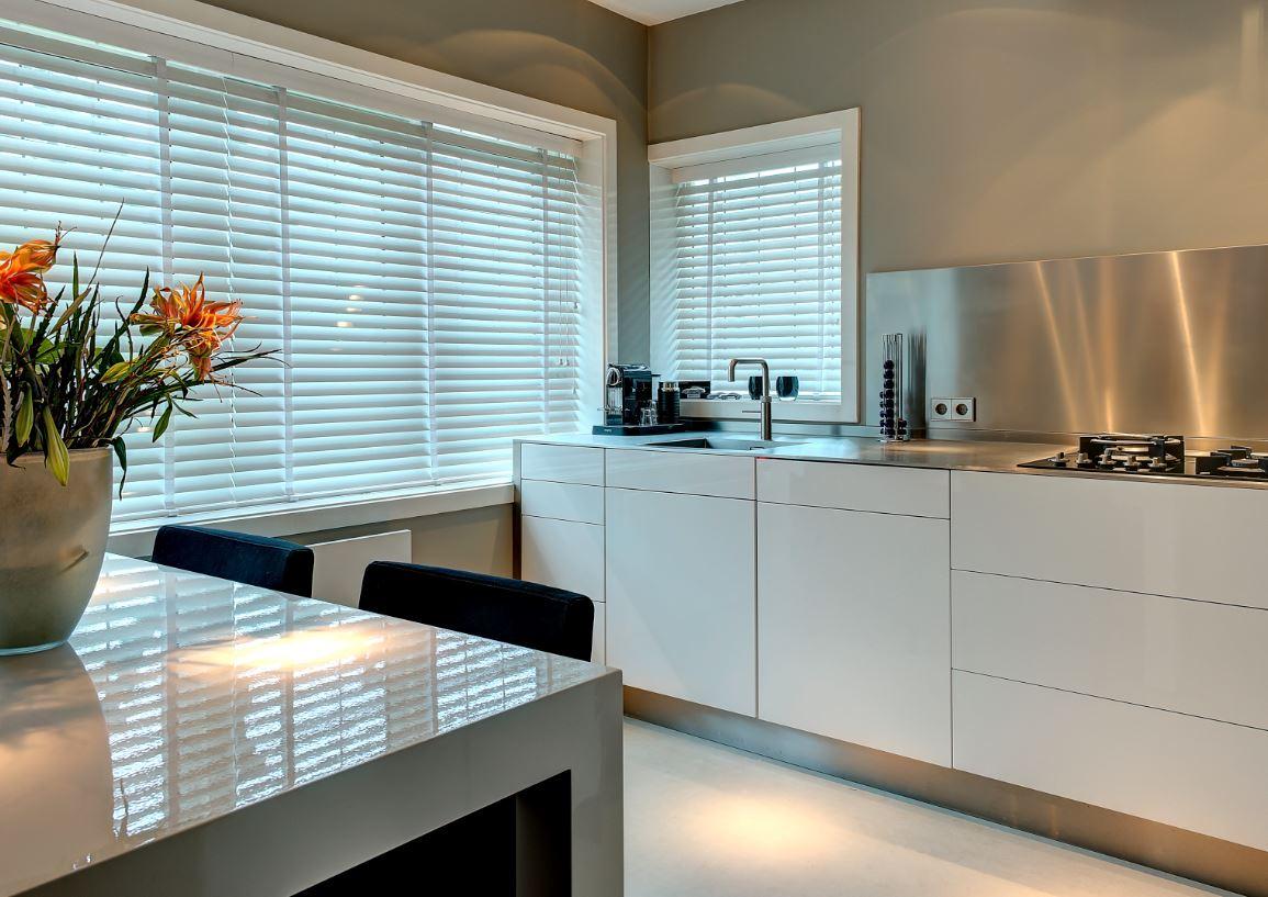 Witte keuken met roestvrij staal keukenblad en achterwand via Dekker Zevenhuizen