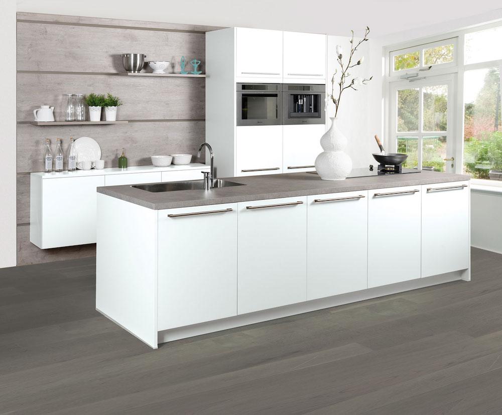 Royale en luxe keuken met moderne apparatuur en kookeiland. Het grijze werkblad staat mooi bij de witte kleur van de strakke opstelling. Keuken Felina van Grando
