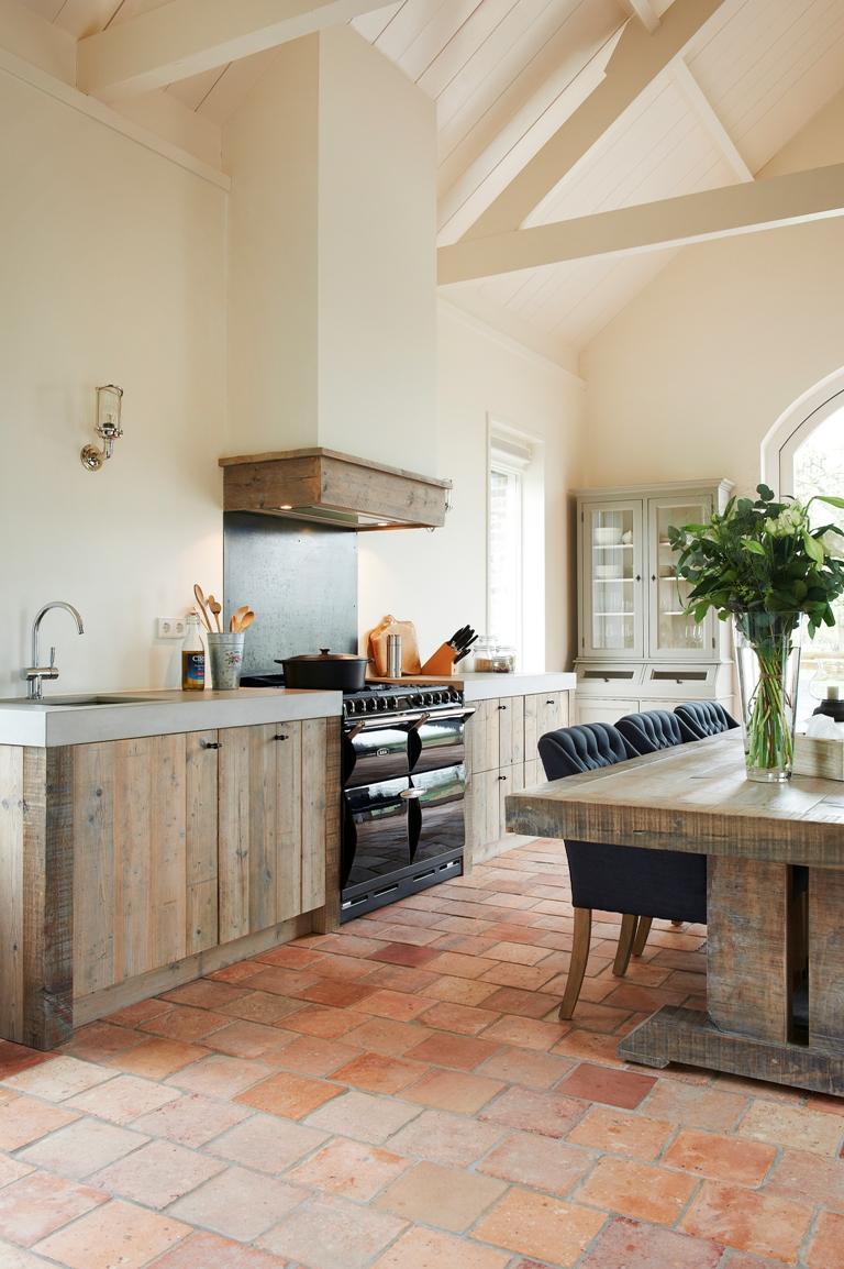 Keuken van oud hout met groot fornuis en vloer van natuursteen via RestyleXL