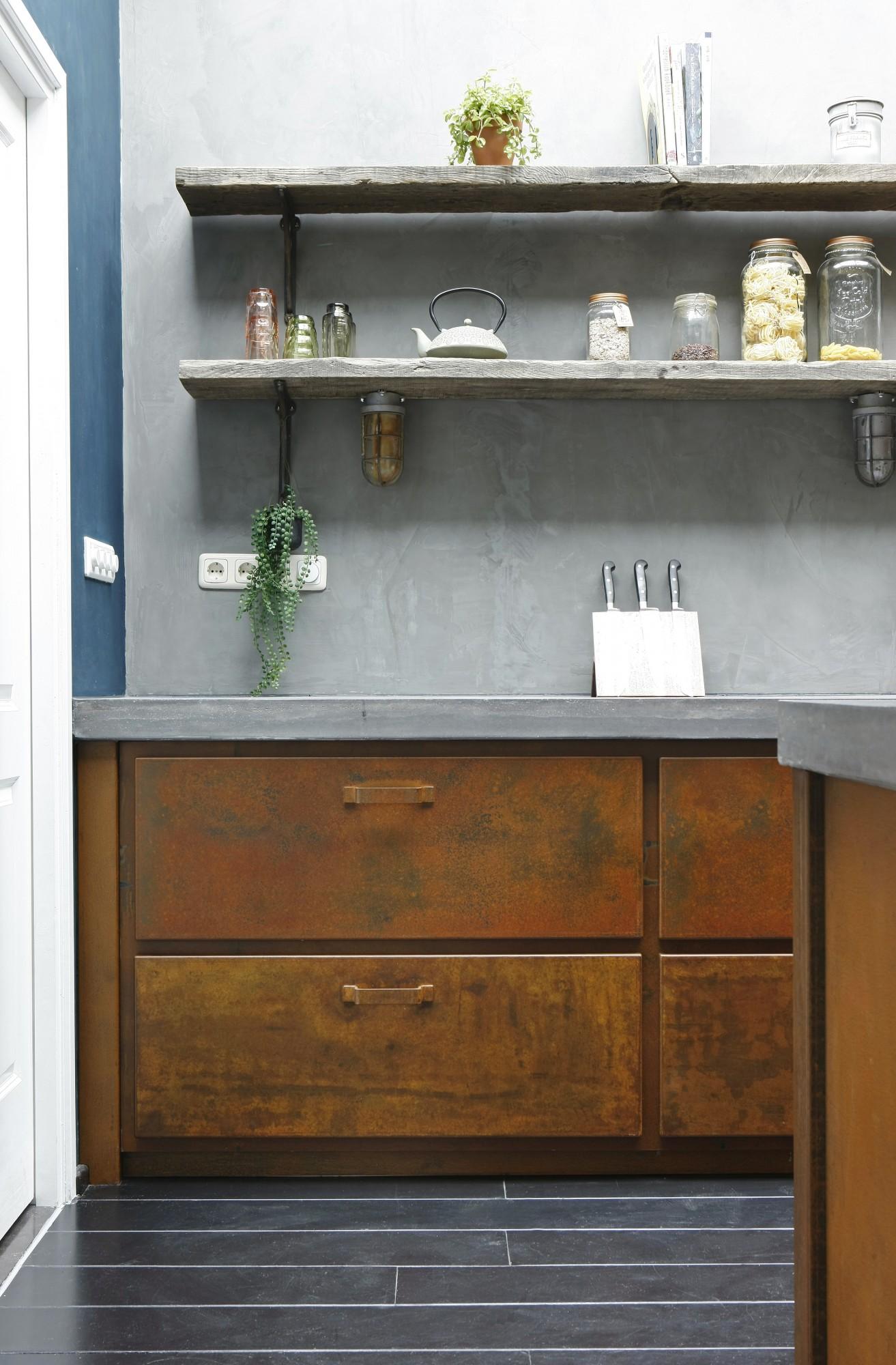Keuken van geroest staal, beton en gerookt eikenhout. Stoere keuken met keukeneiland in landelijke sfeer. Ruw eikenhouten planken aan de wand met betonlook. Jacob Interior keuken Maarn