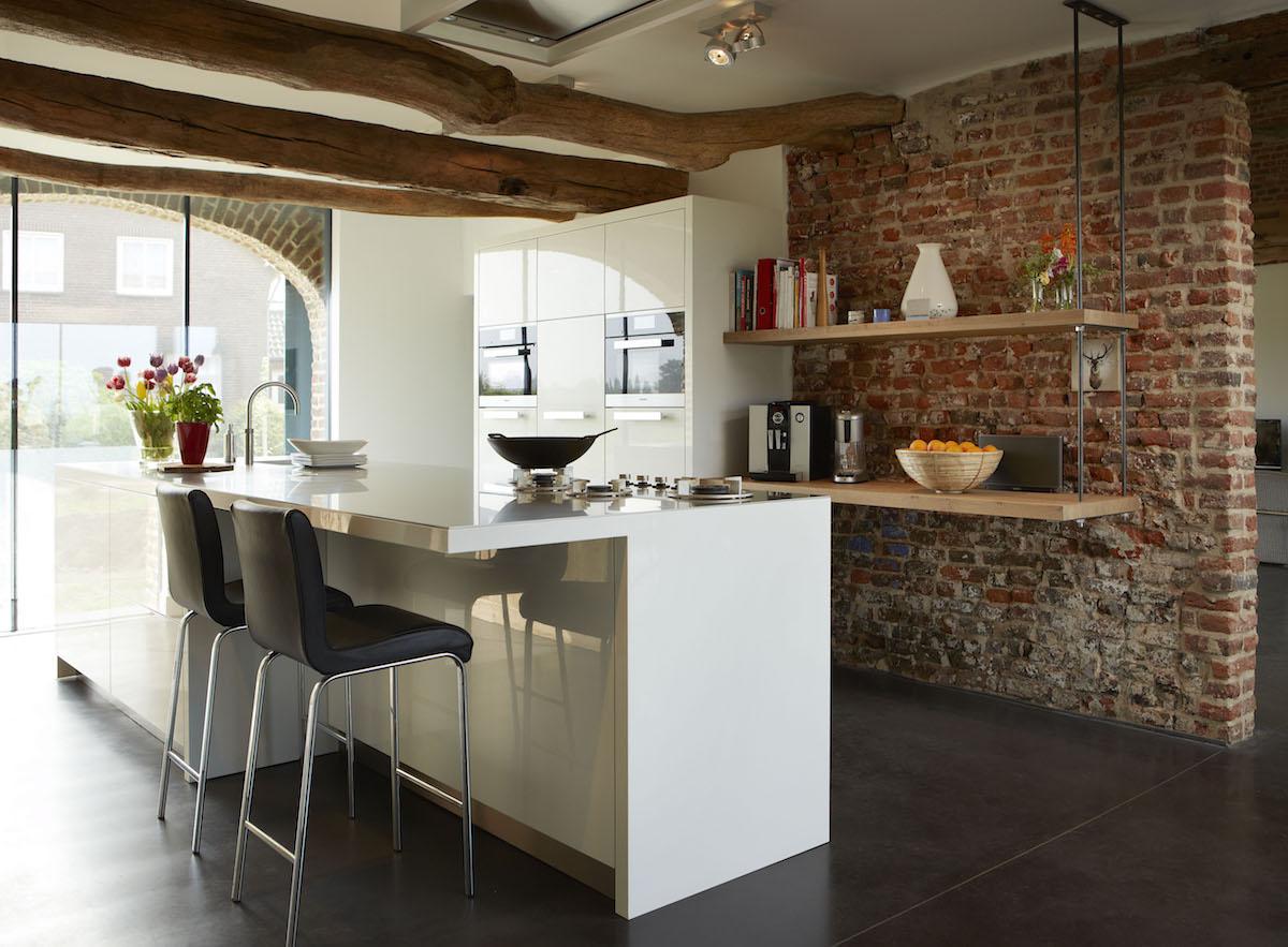 Moderne witte hoogglans keuken met kookeiland en ontbijtbar voorzien van Miele keukenapparatuur. Via Harold Lenssen Keukens