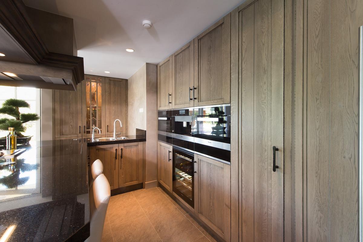 Klassieke houten keuken met bar en moderne Miele apparatuur via Tieleman Keukens