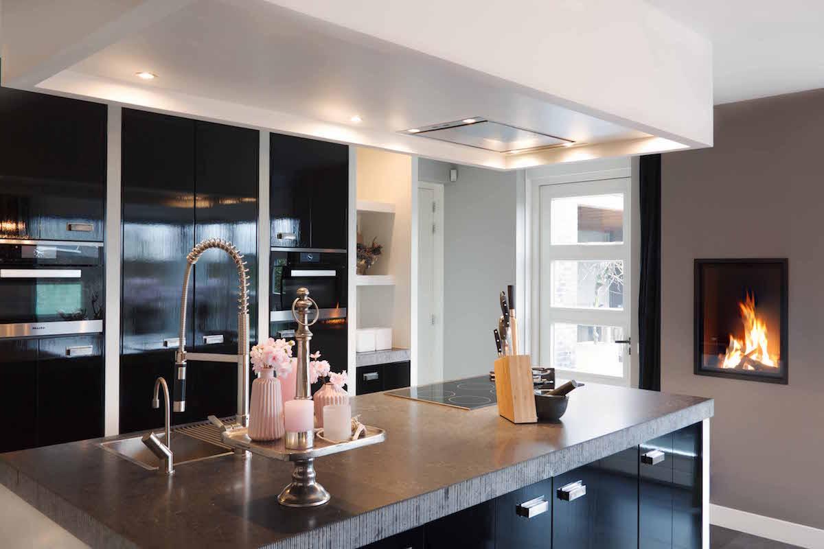 Moderne zwarte designkeuken met Miele apparatuur en open haard via Van Ginkel