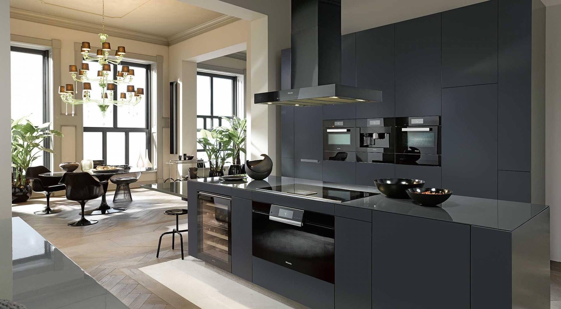Grijze woonkeuken met kookeiland en Miele inbouwapparatuur #woonkeuken #keukentrends #miele #tielemankeukens