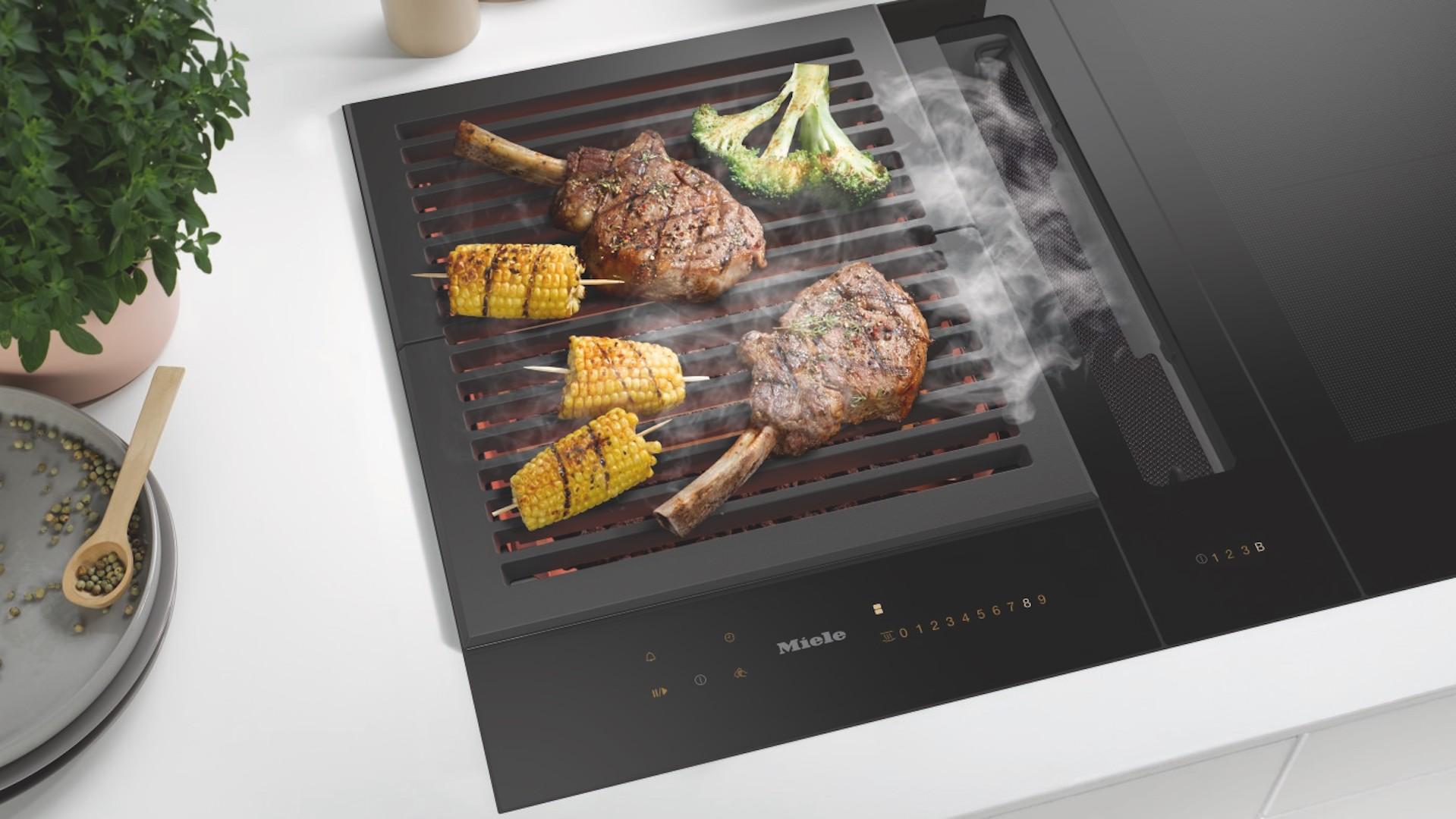 Miele SmartLine kookplaat met verschillende kookelementen zoals een grillrooster en een werkbladafzuiging