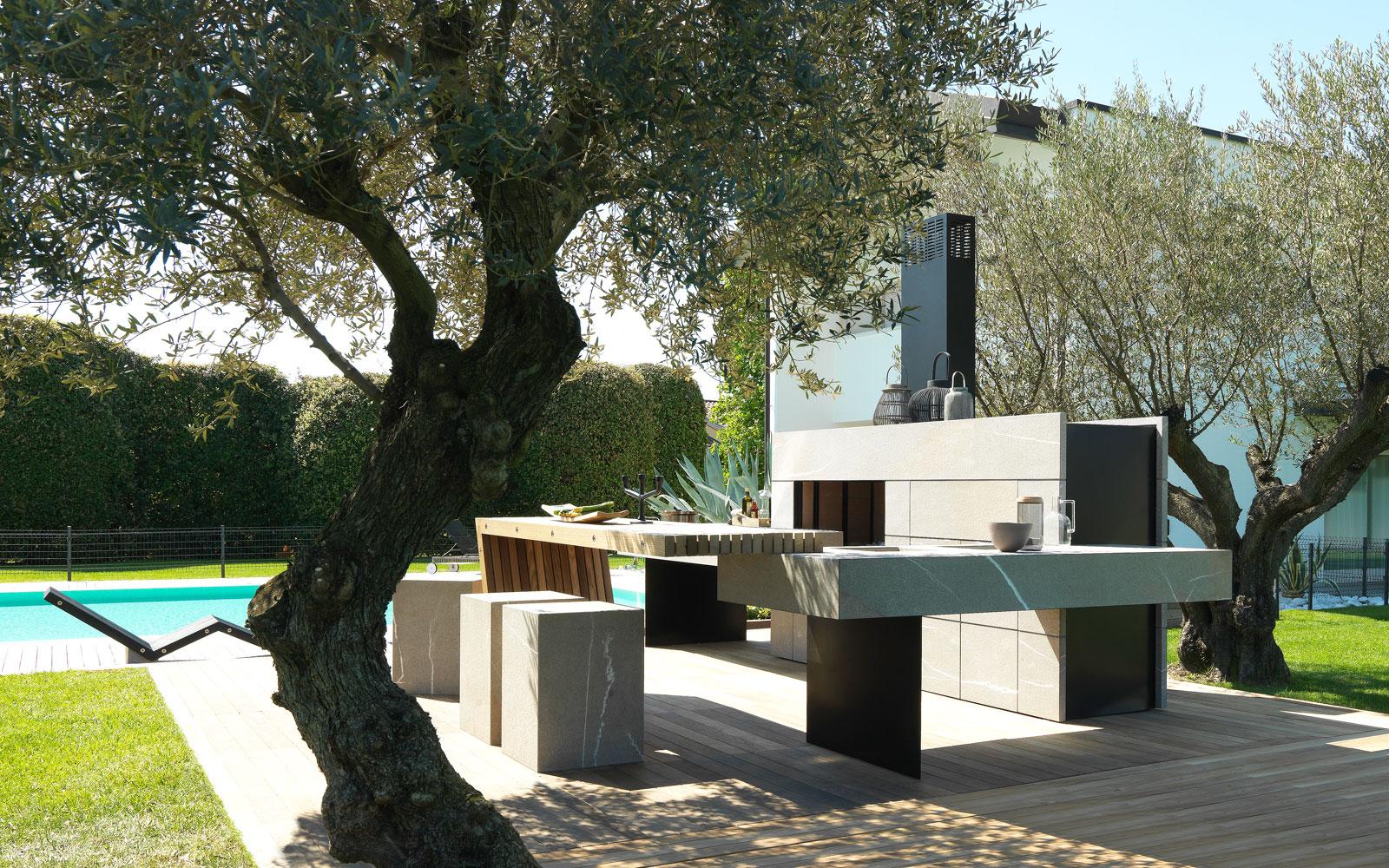 Prachtige Italiaanse buitenkeuken van steen met een houten tafel. Met houtoven, kookmodules, grill, koelkast en koffiezetapparaat. Modulnova #buitenkeuken #tuin #design