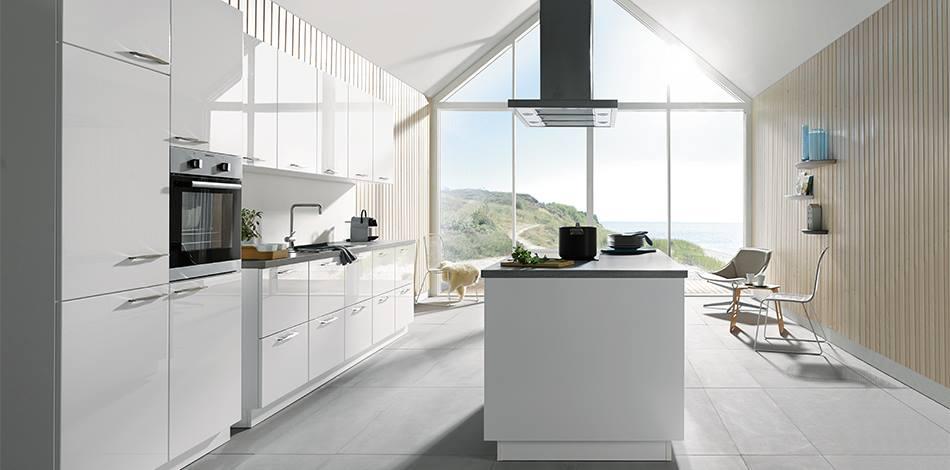 Witte hooglans keuken met grepen op de fronten en kookeiland - Schuller keuken via Tieleman Keukens