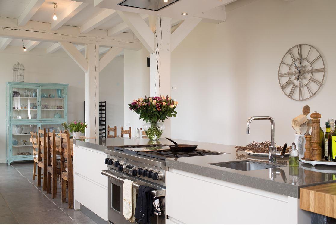 Landelijk kookeiland met fornuis Wolf in landelijke keuken in woonboerderij Katwijk. Geplaatst door Tieleman Keukens