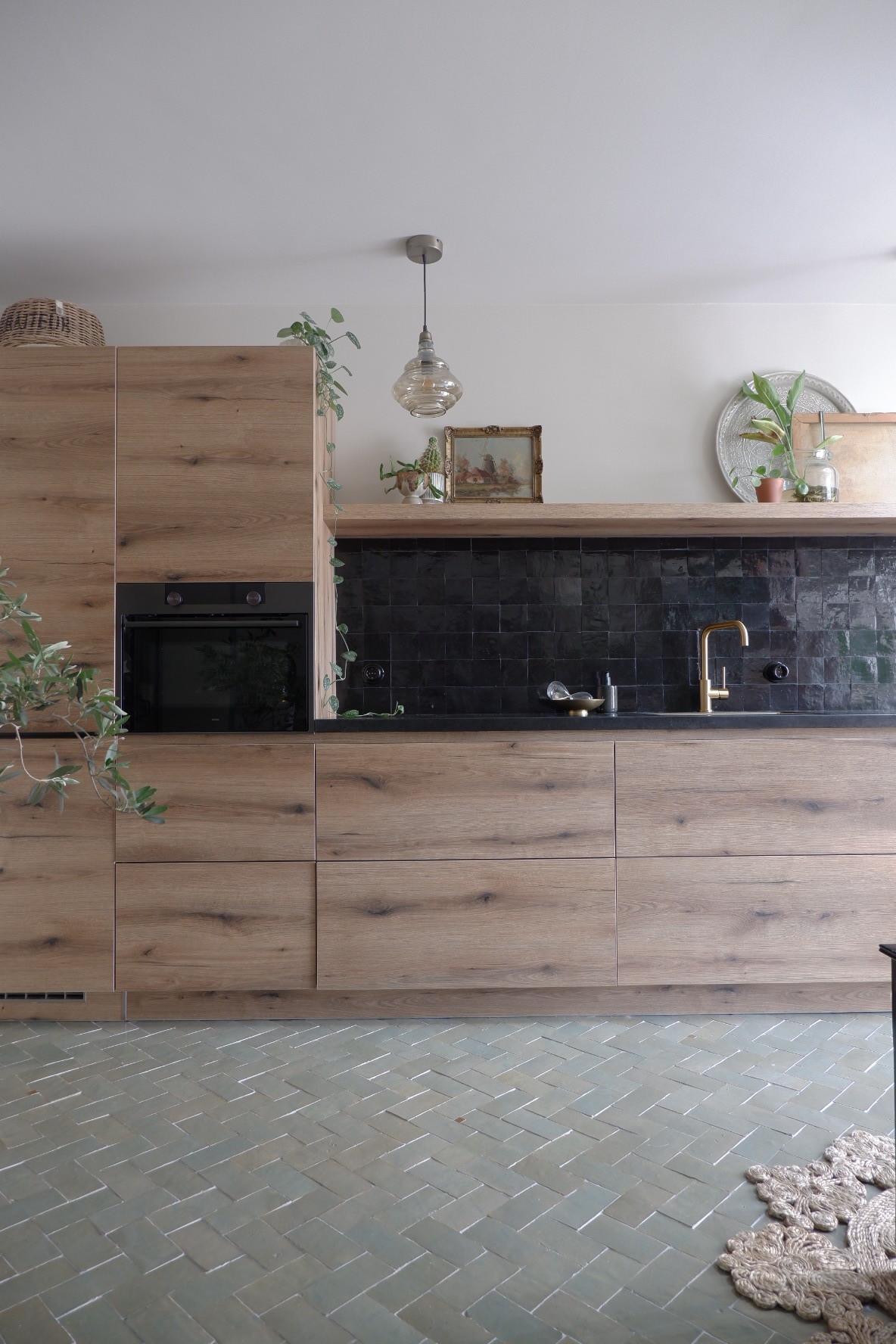 Designtegels houten keuken. Vloertegels Platta Vert Gris Foncee en op de achterwand Zellige Noir #keukentegels #designtegels #tegels #keuken #vloertegels #achterwand #houtenkeuken