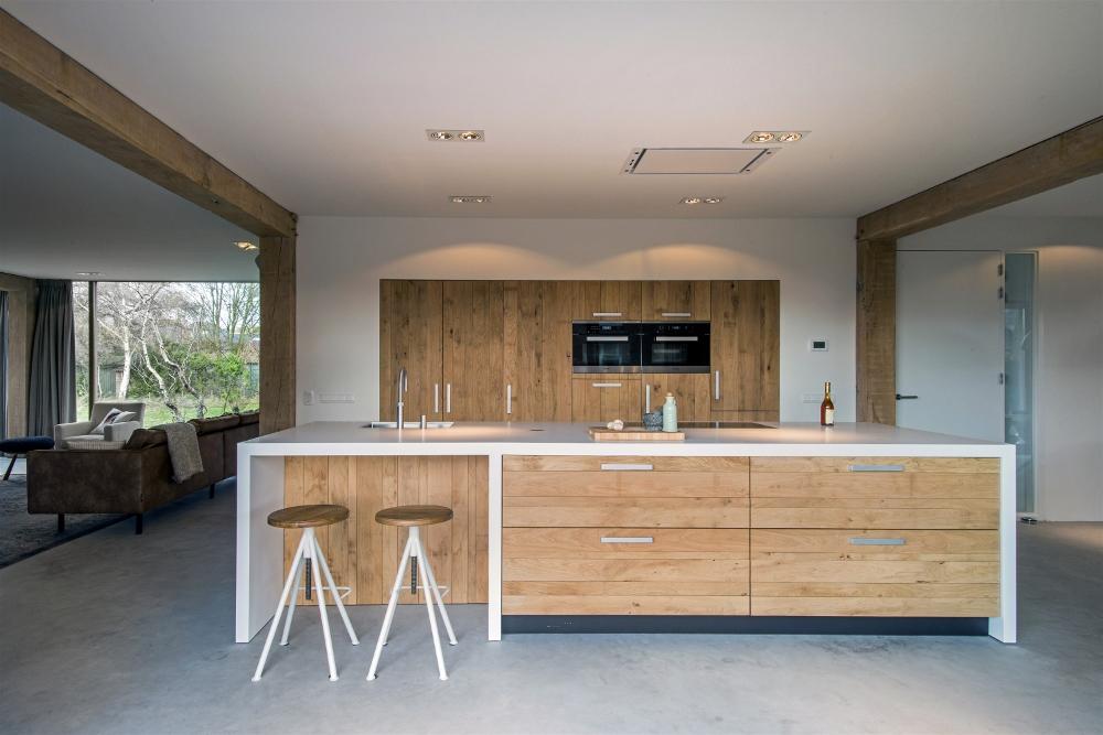 Houten woonkeuken met kookeiland van wit silestone werkblad en ontbijtbar via JP Walker #keuken #kookeiland #houtenkeuken