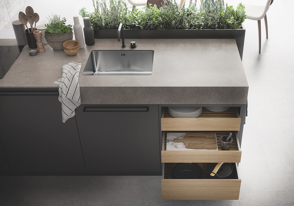 Uit de combinatie van verticale en horizontale structuren en de open en gesloten elementen met lichte en donkere materialen ontstaat een mooie verbinding tussen de lades en de rest van het keukenblok. De kruiden passen weer mooi bij het lichte hout van de fronten. SieMatic