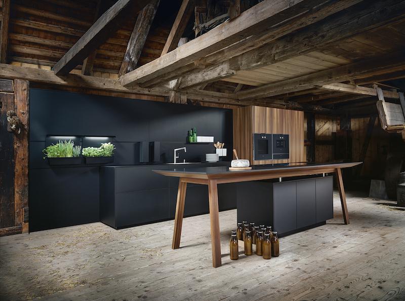next125 zwarte keuken met Feniks fronten en werkblad. Kooktafel met onyx feniks blad en larix houten onderstel. Ook de hoge kasten hebben fronten van larix hout. De greeploze keuken met tip on heeft anti-fingerprint coating en next125 paneeltuinen met groeilampen voor het next125 Cube Systeem in onyx zwart #next125 #designkeuken #keuken #innovatie #eurocucina #eurocucina2018