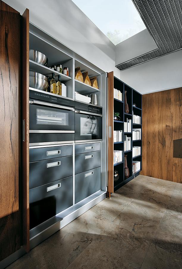 Hoge keukenkast met draaibare deuren waarachter keukenapparaten en inbouwapparatuur verborgen is. Keuken NX902 van next125