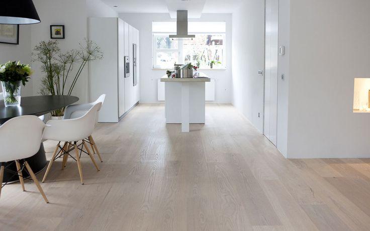 Open witte woonkeuken met kookeiland en doorgetrokken houten vloer van Uipkes