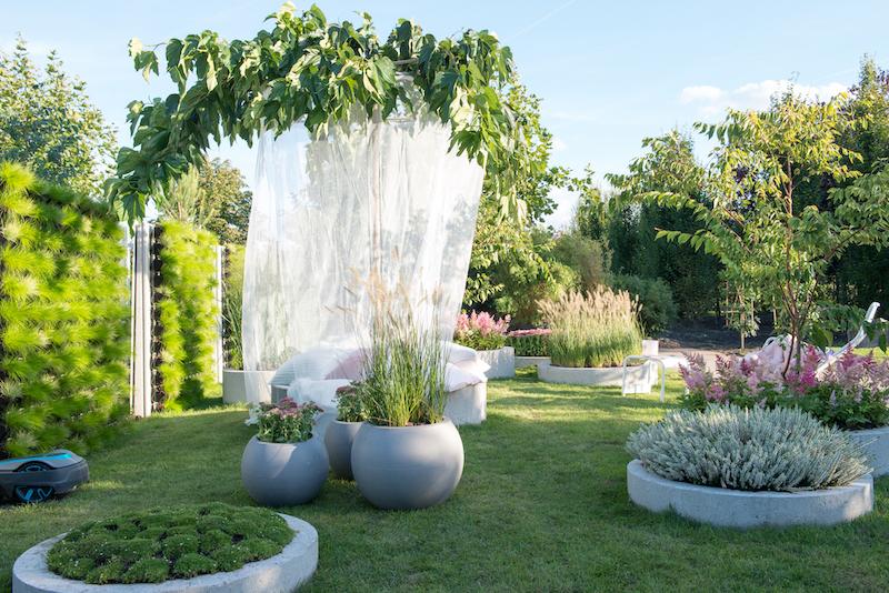Tuintrend 2019 - In de tuin 'Soft Landing' zie je daarom veel ronde vormen, lekkere kussens en aaibare beplanting. Een groene plek waarin je heerlijk tot rust kunt komen en die je het gevoel geeft dat je door een enorm kussen wordt opgevangen. In deze trendtuin tuin overheersen vriendelijke pasteltinten. Het gazon speelt een belangrijke rol. Niet alleen een plek om met blote voeten te betreden maar ook praktisch: regenwater zakt, in tegenstelling tot een betegelde tuin, direct weg in de bodem #tuintrend #trendtuin #tuininspiratie #tuinen #groen #tuinplanten #tuinidee #2019