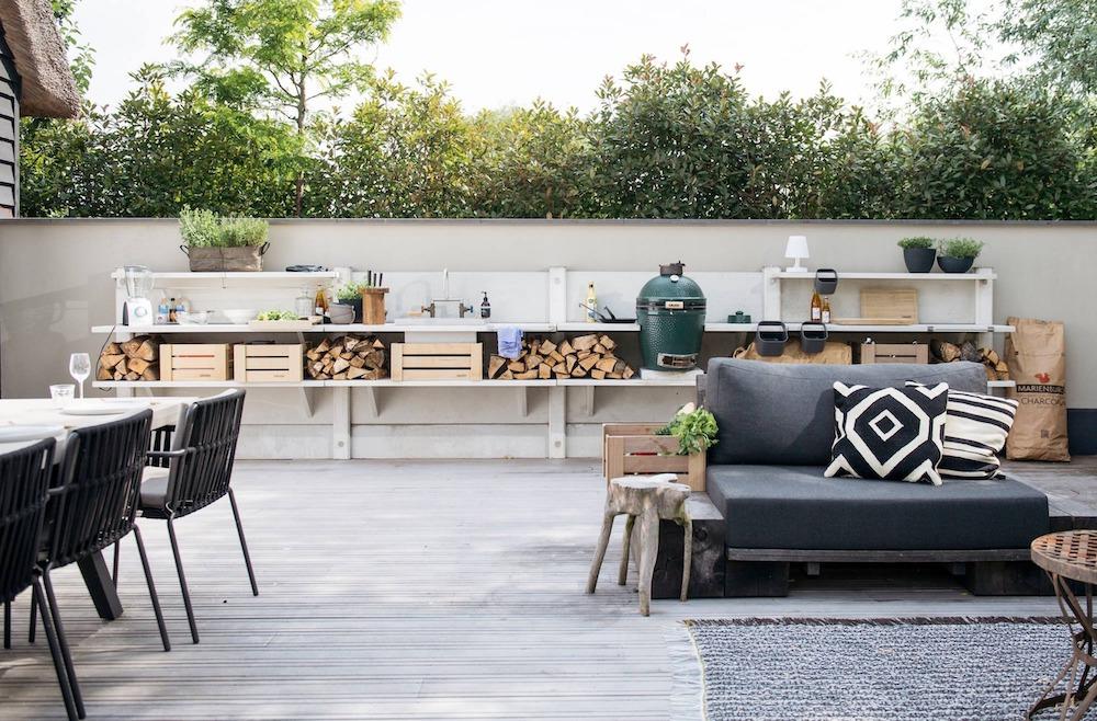 Buitenkeuken WWOO met loungebanken en green egg barbecue. #tuininspiratie #buitenkeuken #barbecue #terras #loungeset #wwoo