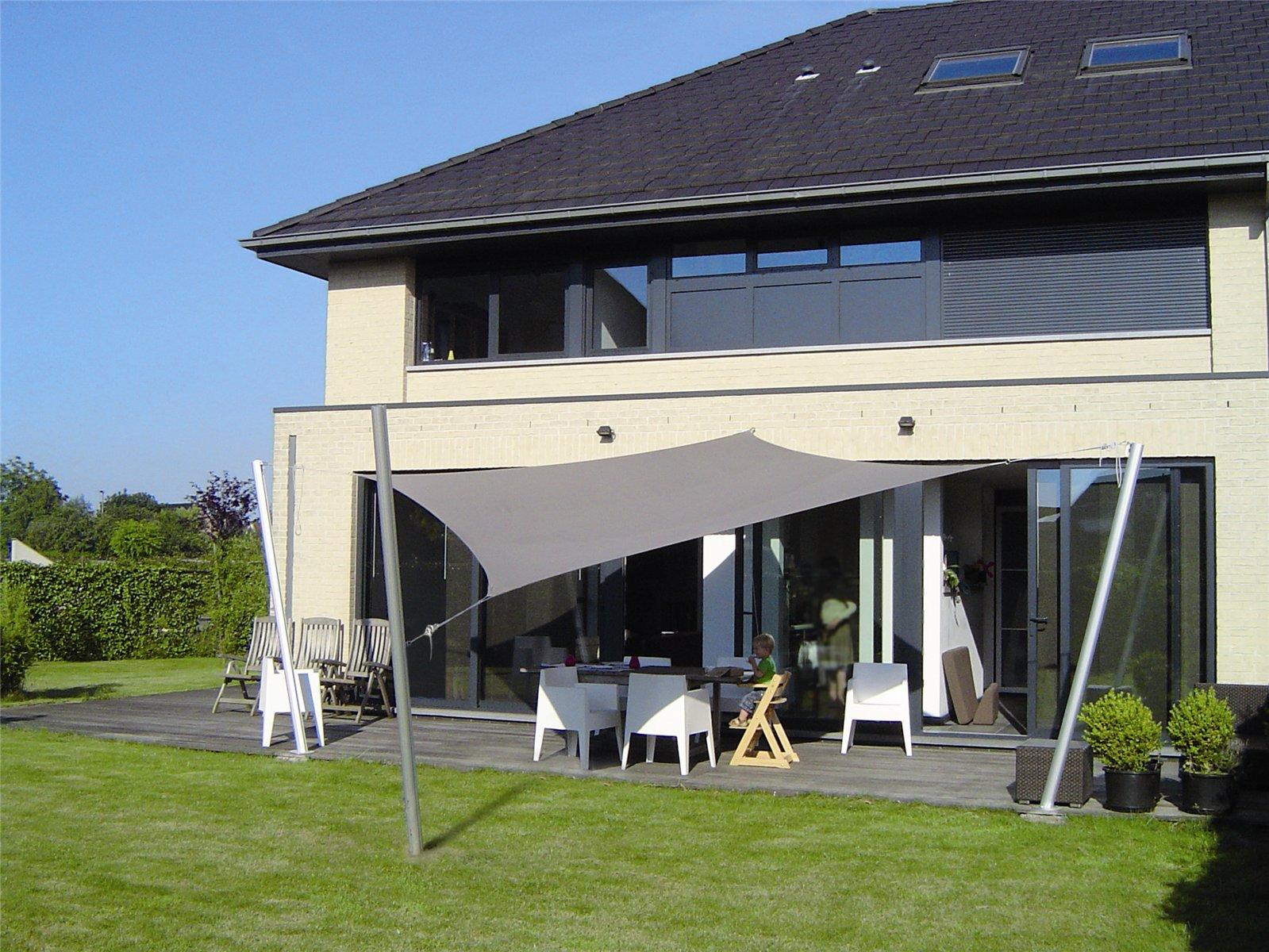 Een schaduwdoek boven het terras biedt veel schaduw en verandert zomerse warmte in een aangename temperatuur met verzachtend licht. Via ZonZ schaduwzeilen