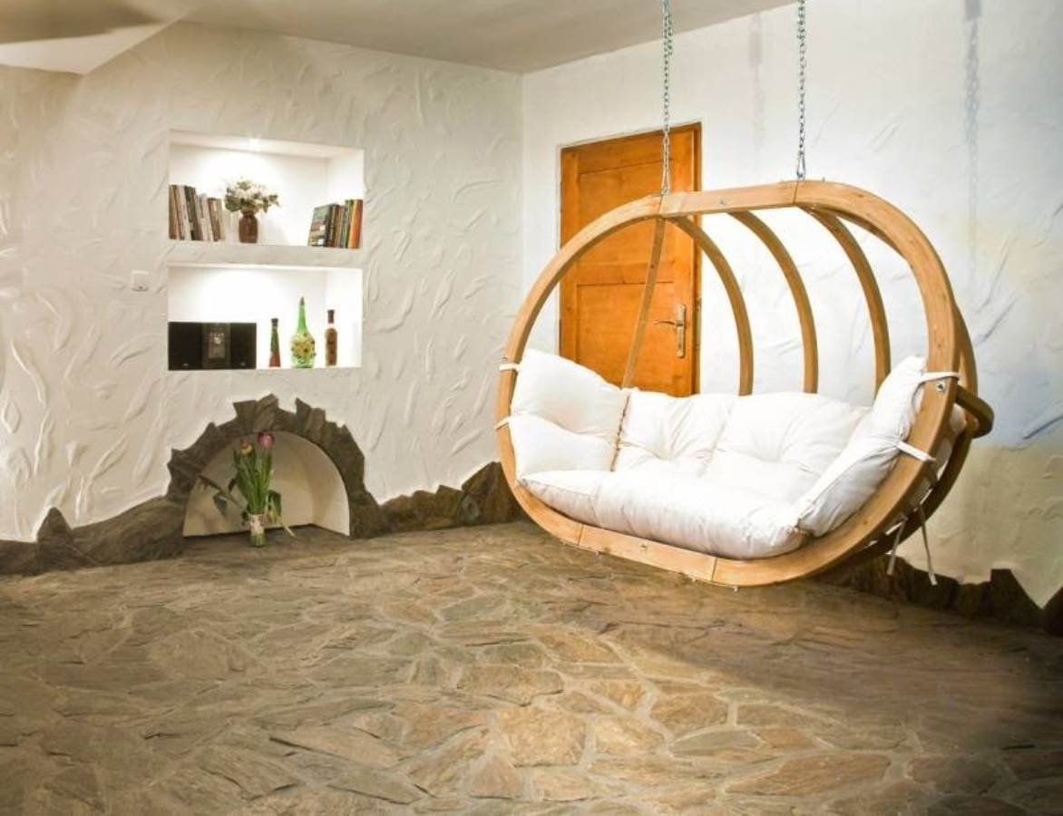 Terras met natuursteen vloer van Nibo Stone en luxe tweepersoons hangstoel van Living Luxury
